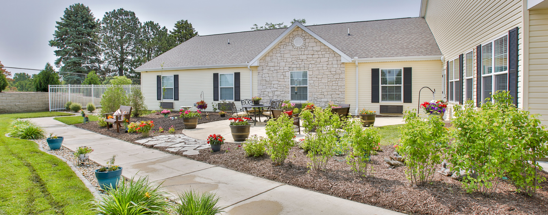 Residents with dementia can enjoy a traveling path, relaxed seating and raised garden beds in the courtyard at Bickford of Bloomington