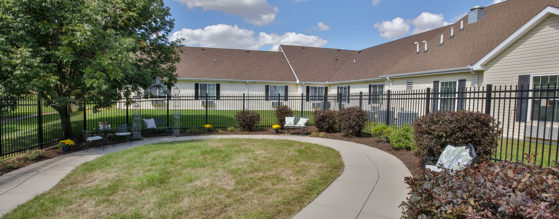 Residents with dementia can enjoy a traveling path, relaxed seating and raised garden beds in the courtyard at Bickford of Champaign